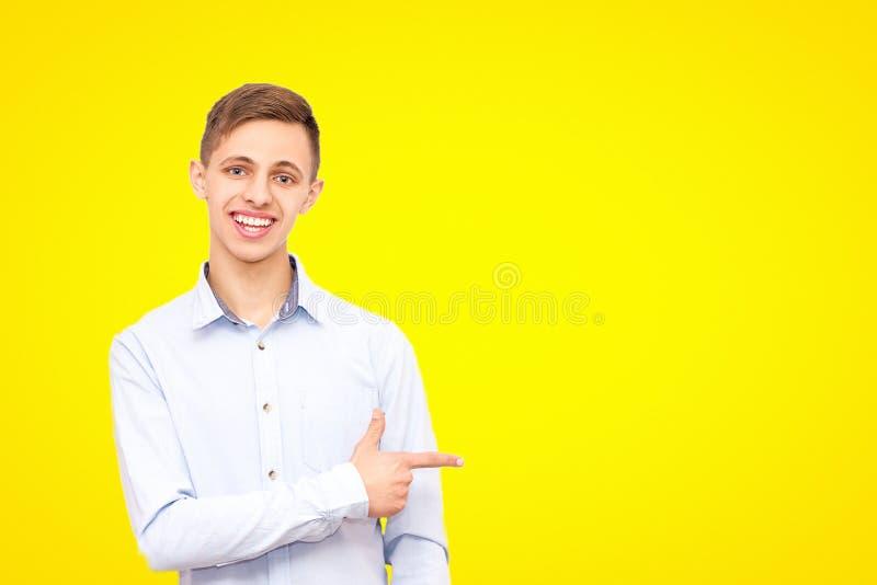 Facet w błękitnej koszula reklamuje produkt, odizolowywającego na żółtym tle obraz stock