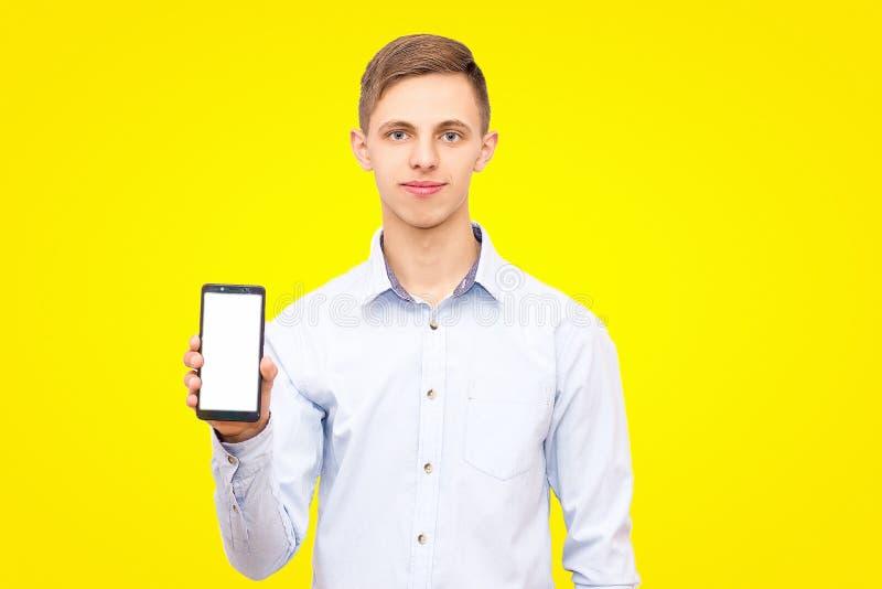 Facet w błękitnej koszula reklamuje telefon odizolowywającego na żółtym tle obrazy stock