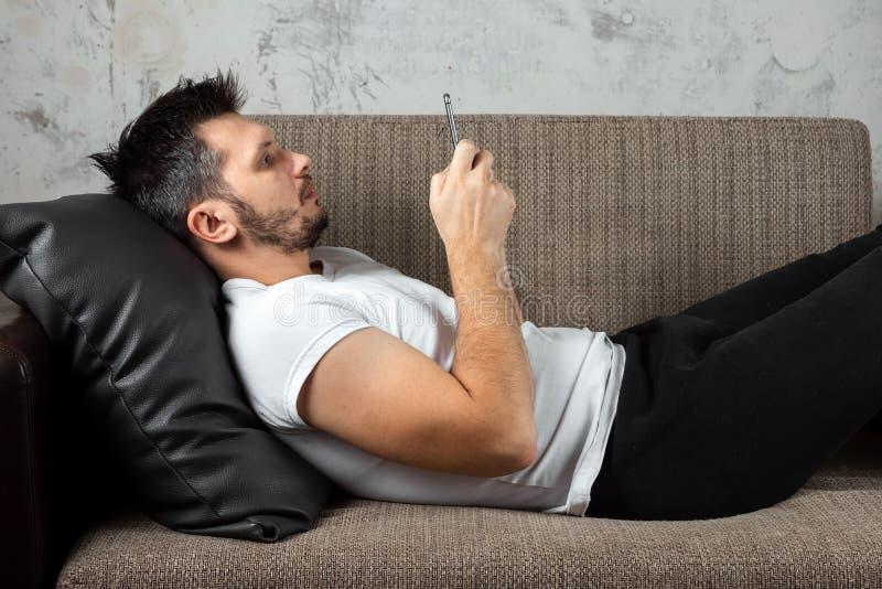 Facet w białej koszula kłama na obsiadaniu w telefonie i leżance Pojęcie gnuśność, apatia fotografia stock