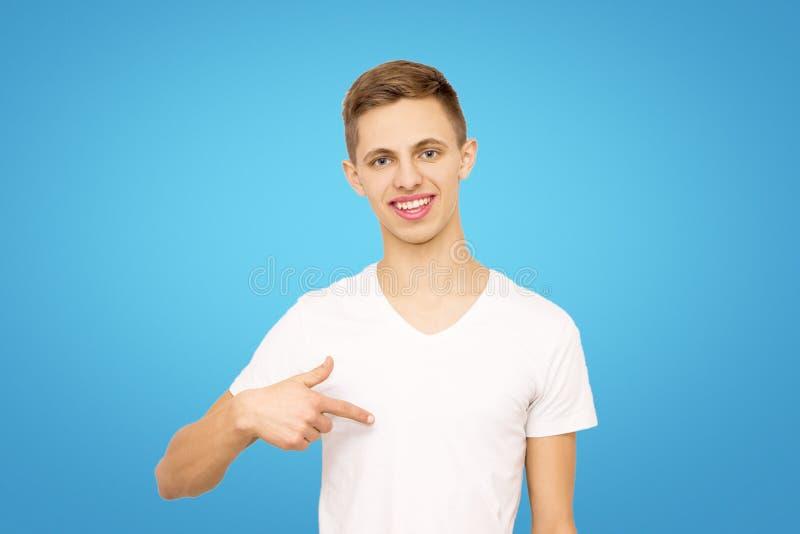 Facet w białej koszulce pokazuje jego palec przy on w studiu zdjęcie stock