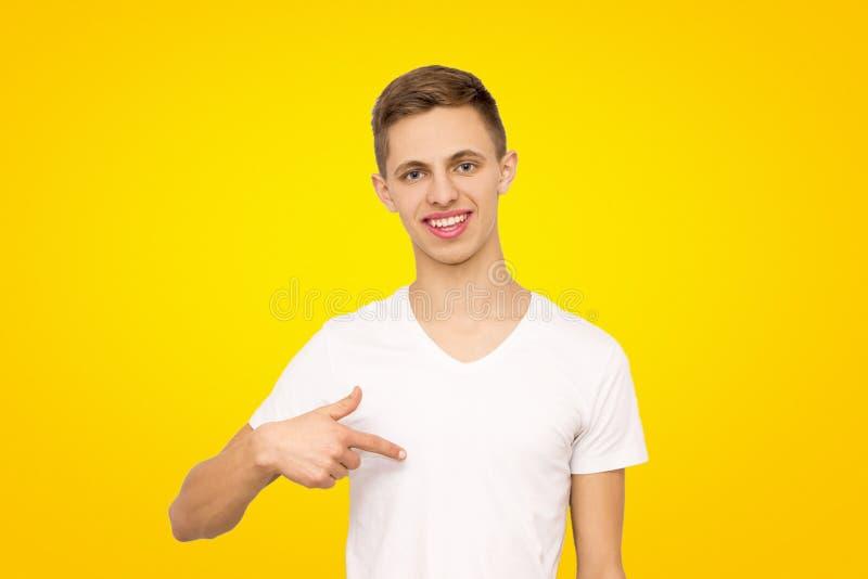 Facet w białej koszulce pokazuje jego palec przy on w studiu zdjęcie royalty free