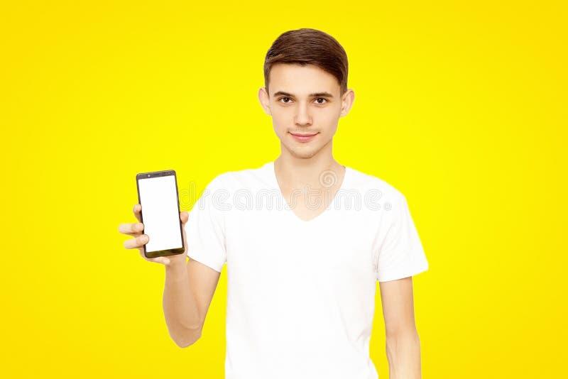 Facet w białej koszulce reklamuje telefon na żółtym tle, zdjęcie royalty free