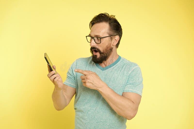 Facet?w eyeglasses rozochocony wskazywa? przy smartphone M??czyzna u?ytkownika antrakta szcz??liwy zastosowanie dla smartphone M? obrazy royalty free