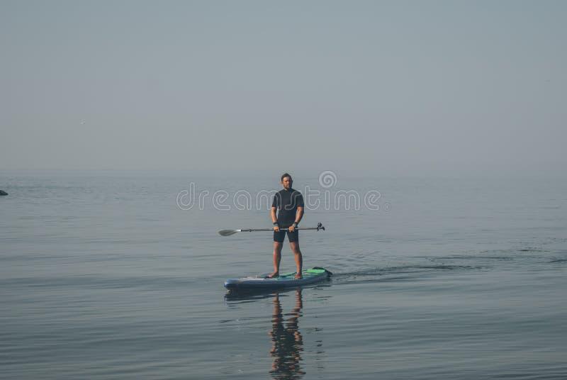 Facet w wetsuit na desce z wiosłem, odpoczynek na morzu zdjęcia stock