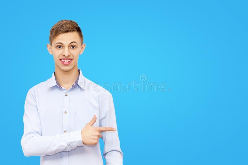 Facet wskazuje palec przy reklamą na błękitnym tle, mężczyzna reklamuje produkt zdjęcia stock