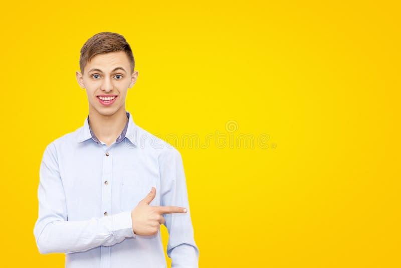 Facet wskazuje palec przy reklamą, odizolowywającą na żółtym tle, mężczyzna reklamuje produkt zdjęcie royalty free