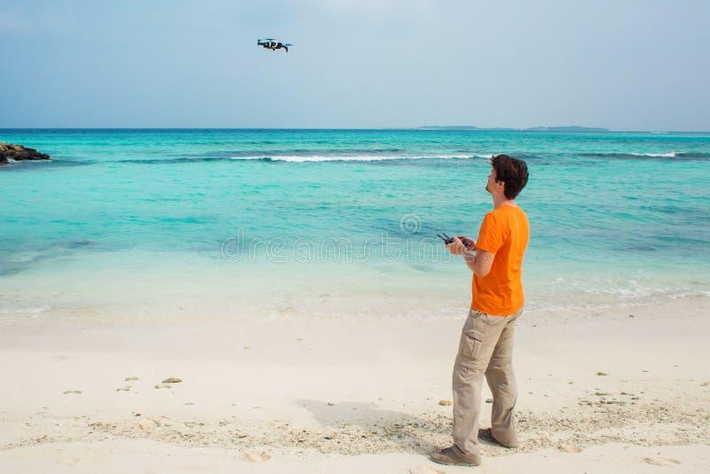 Facet wszczyna trutnia nad morza, fotografii i wideo strzelaniną na quadrocopter/, obraz stock