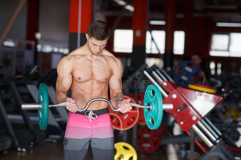 Facet z barem robi ćwiczeniom na zamazanym tle gym zdjęcie royalty free