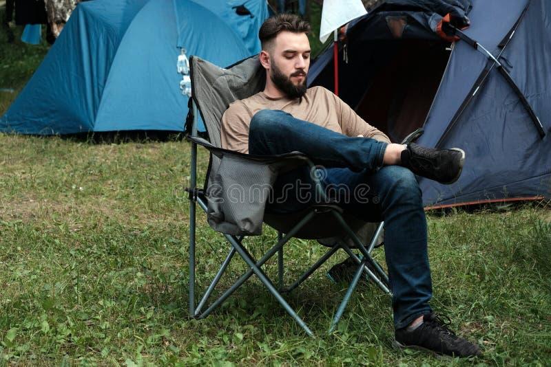 Facet z brodą w cajgach i koszulce siedzi na falcowania krześle blisko namiotów Pojęcie mężczyzny czas wolny wewnątrz zdjęcie royalty free