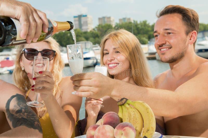 Facet z dwa dziewczynami pije szampana na jachcie zdjęcia stock