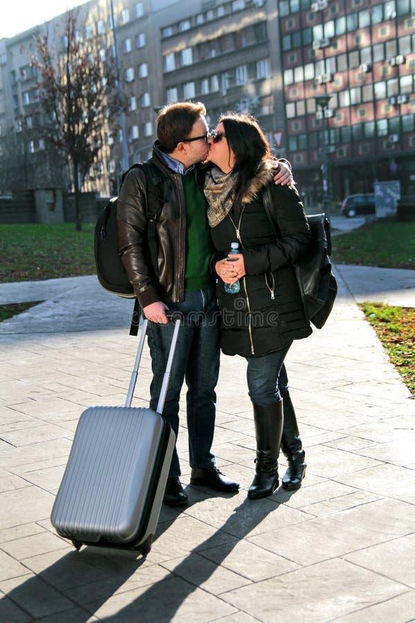 Facet z dziewczyną i walizką całuje w parku fotografia stock