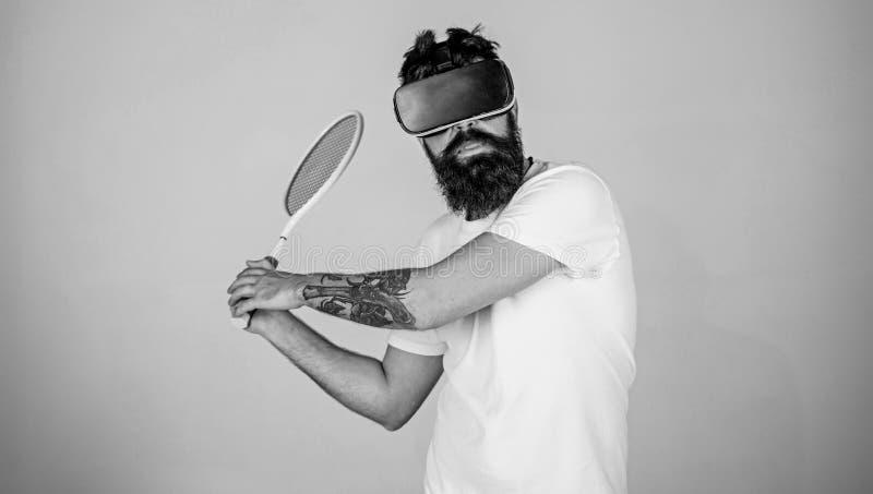 Facet z VR szk?ami bawi? si? tenisa z kantem i pi?k? M??czyzna z brod? w VR szk?ach bawi? si? tenisa, popielaty t?o modni? fotografia royalty free