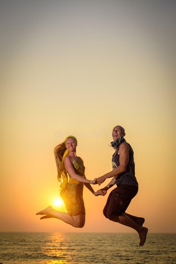 Faceta i dziewczyny doskakiwanie w powietrzu na tle Młoda szczęśliwa para skacze na plaży zdjęcia stock