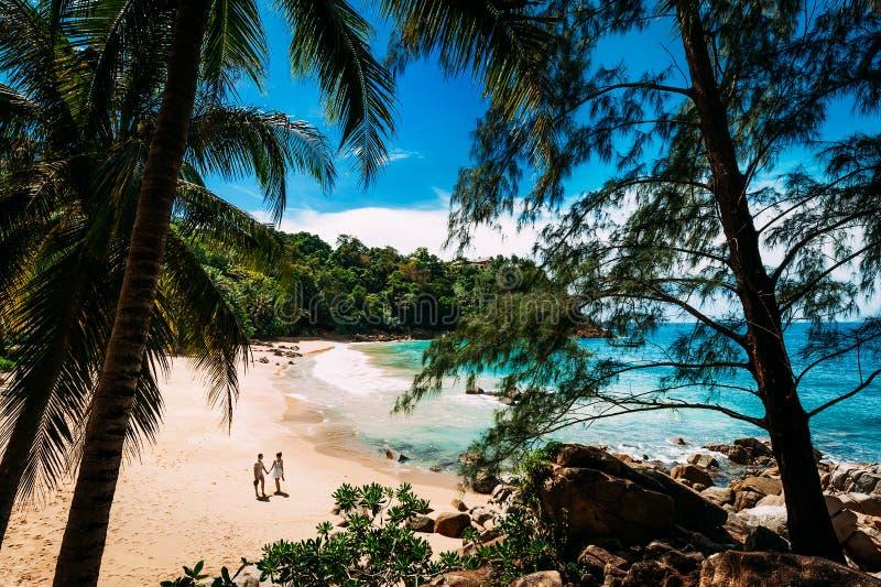 Faceta i dziewczyny mienia odprowadzenie na plaży i ręki obrazy stock