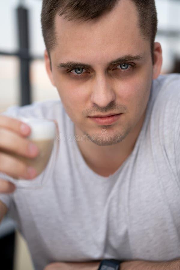 Faceta przebijania spojrzenie M?ody facet siedzi w kawiarni obrazy stock
