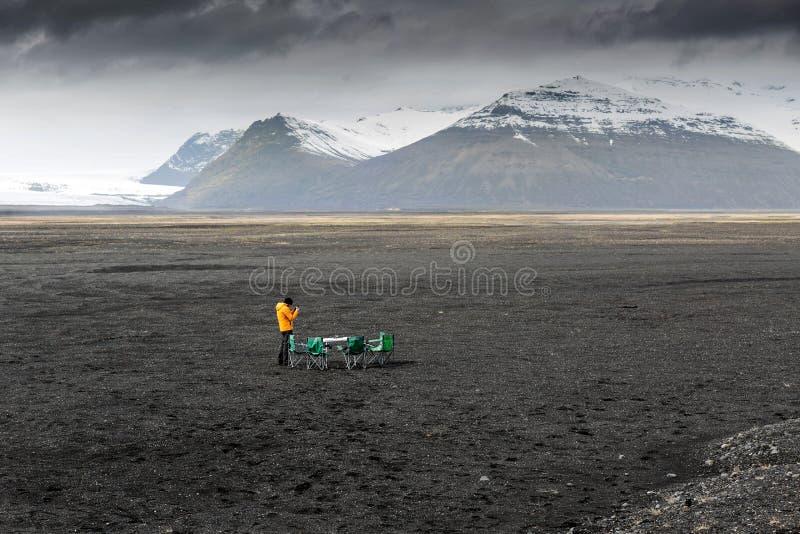 Faceta turysta układał pinkin na czarnym piasku w górach zdjęcie stock
