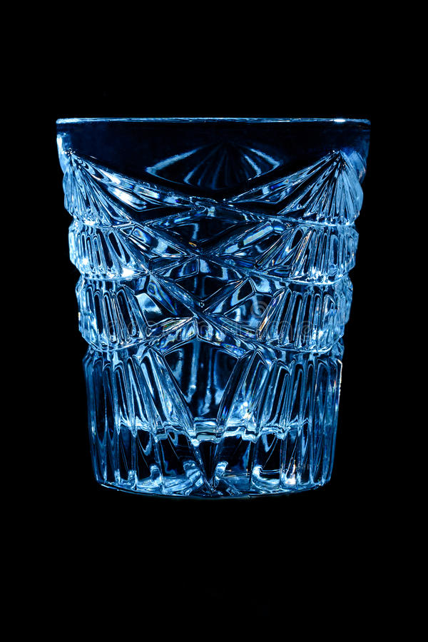 Faceted clear crystal empty glass on a black background royalty free stock image