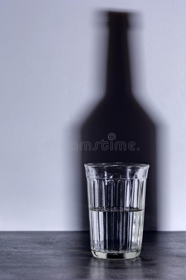Glass and the shadow of a bottle of vodka stock photos