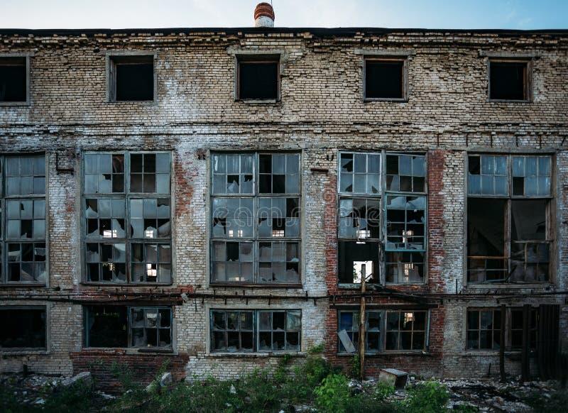Fachada abandonada del edificio industrial, ventanas rotas, paredes lamentables imágenes de archivo libres de regalías