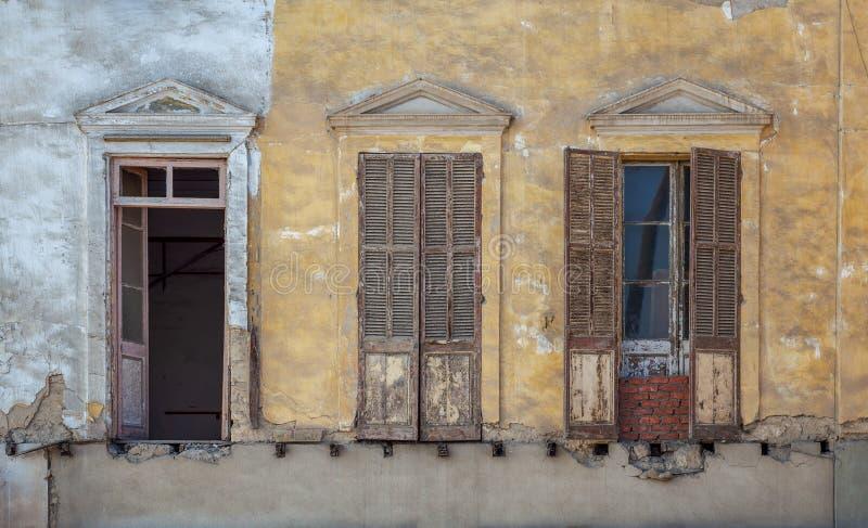 Fachada abandonada envejecida de la casa del grunge del vintage con las ventanas quebradas y los obturadores resistidos fotos de archivo