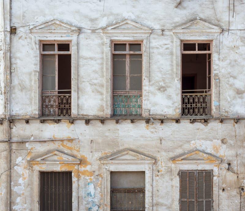 Fachada abandonada envejecida de la casa del grunge del vintage con las ventanas quebradas y los obturadores resistidos foto de archivo