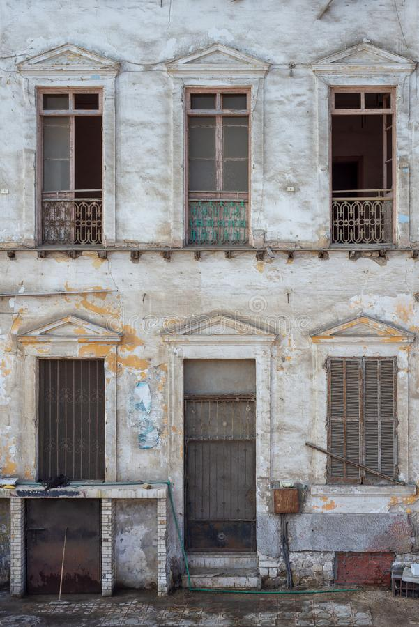 Fachada abandonada envejecida de la casa del grunge del vintage con la puerta y ventanas quebradas y obturadores resistidos imágenes de archivo libres de regalías