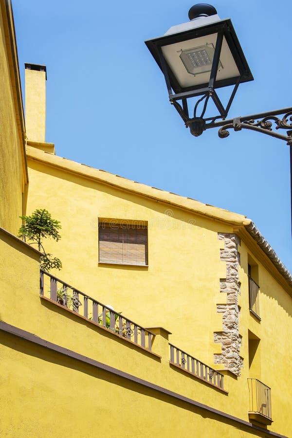 Fachada amarilla rústica contra un cielo azul del verano en una pequeña ciudad mediterránea al lado de Barcelona Destinación del  imagen de archivo