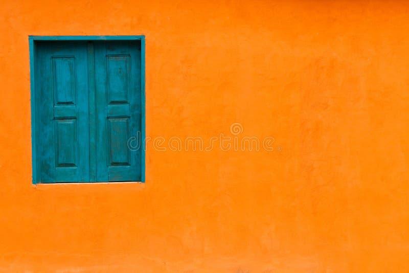 Fachada anaranjada brillante viva del color con la ventana azulverde y la textura anaranjada vacía grande de la pared imagenes de archivo