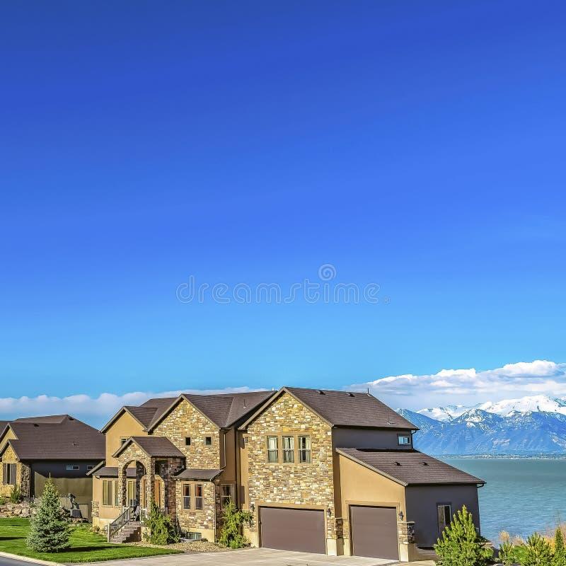Fachada bonita do quadrado das casas com gramados ajardinados ao longo de uma estrada pavimentada foto de stock