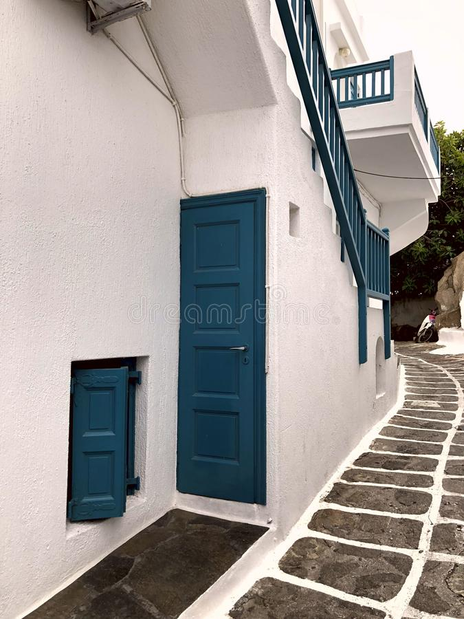 Fachada branca colorida da casa com portas, a escadaria e o balcão mar-verdes na ilha de Mykonos foto de stock