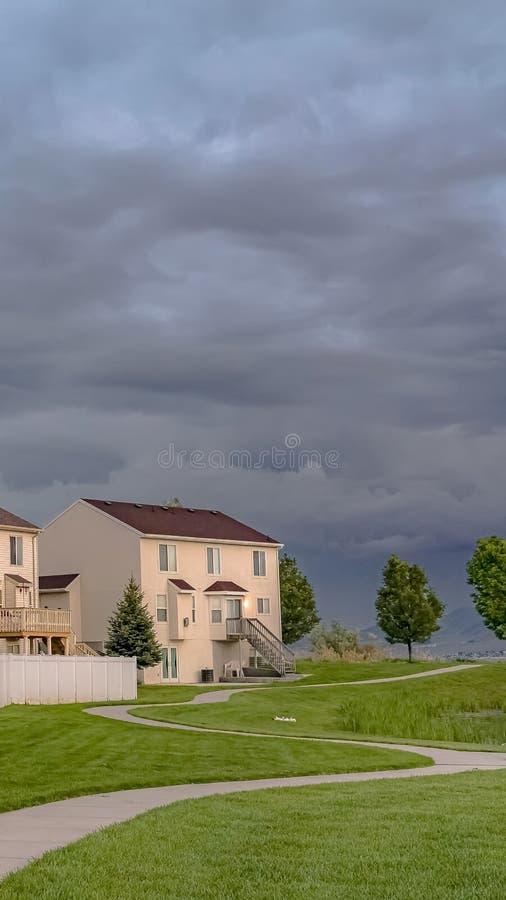 Fachada casera vertical que pasa por alto un campo verde expansivo con un camino y una charca pavimentados fotografía de archivo libre de regalías