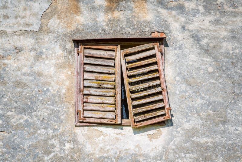 Fachada com janela de uma casa abandonada velha com madeira resistida imagens de stock