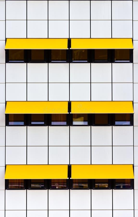 Fachada com telhas brancas e os toldos amarelos imagem de stock
