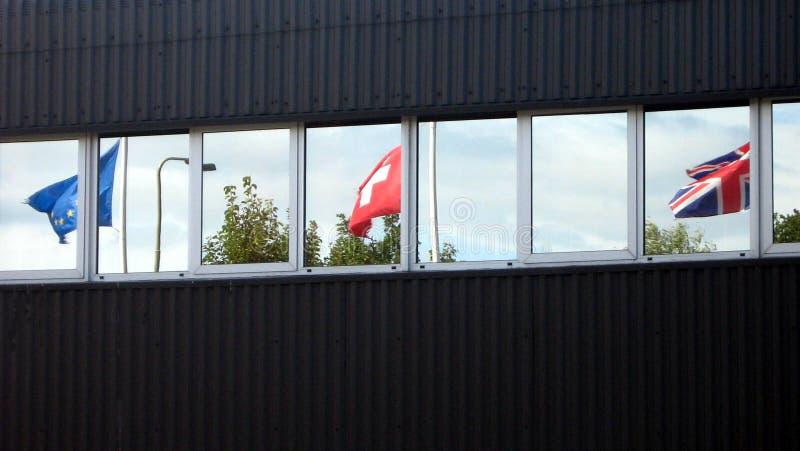 Fachada con la reflexión de banderas imagenes de archivo