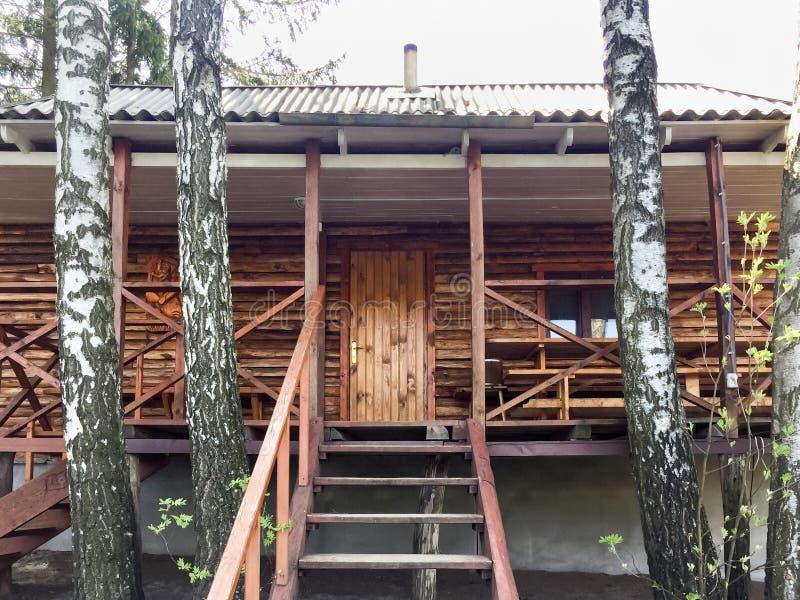 Fachada da casa de campo de madeira do verão na máscara das árvores fotos de stock royalty free