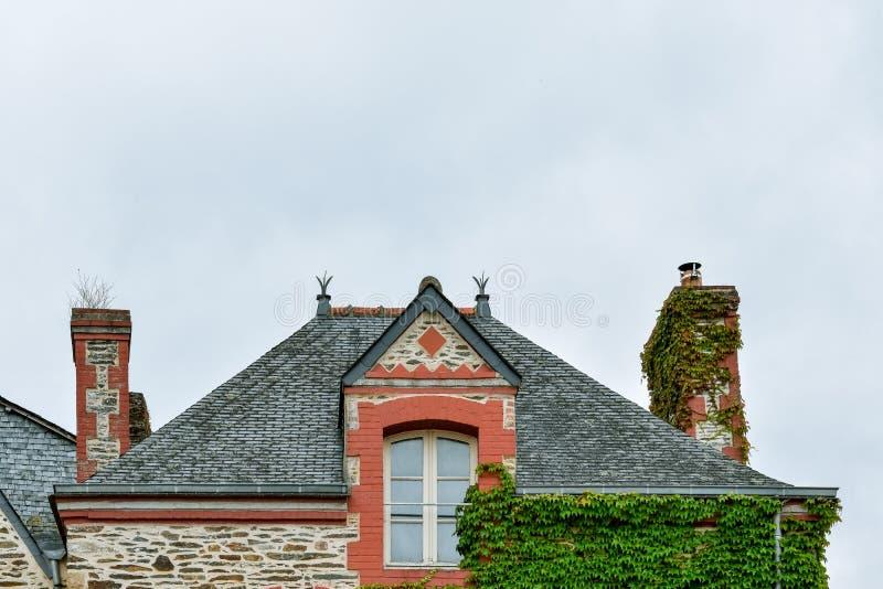 Fachada da casa, do telhado e da janela coloridos velhos do sótão em Rochefort-en-Terre, Brittany francês fotos de stock
