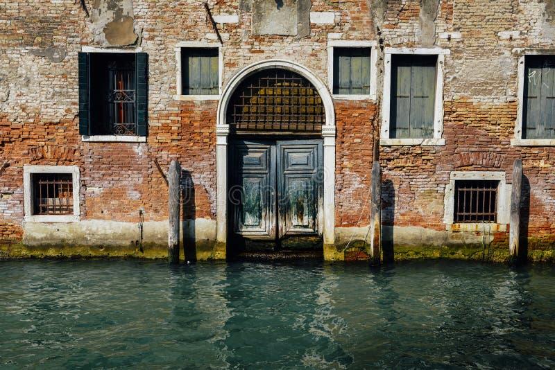Fachada da casa velha parcialmente musgoso do tijolo com a porta de madeira do vintage no canal estreito em Veneza, Itália fotografia de stock royalty free