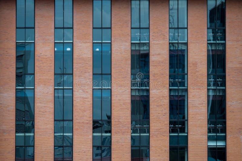 Fachada da construção de tijolo com um vidro azul para a textura foto de stock