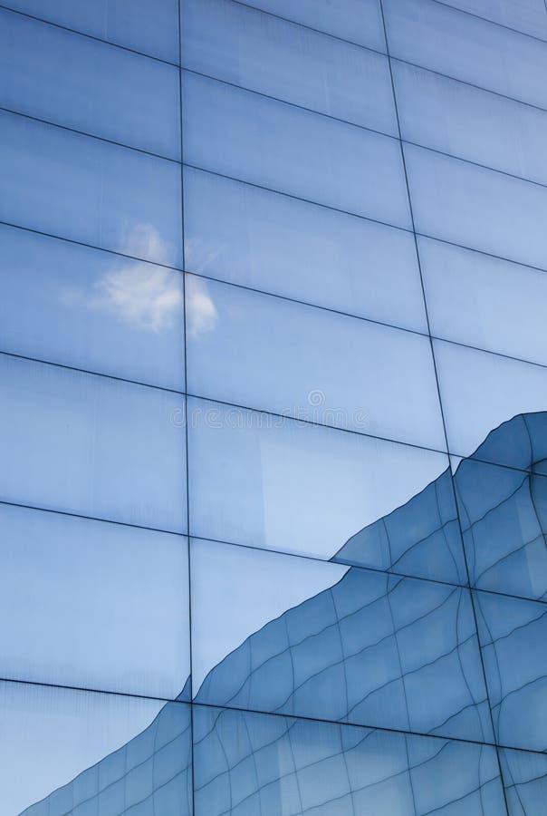 Fachada da construção de vidro moderna com reflexões do céu azul e imagem de stock