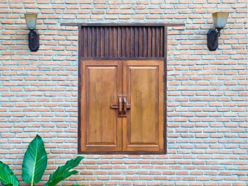 Fachada da parede de tijolo velha da construção com a lanterna e a folha de madeira da janela fotografia de stock