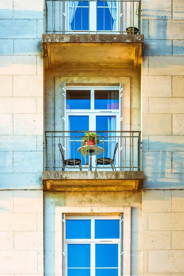Fachada de construção com janelas e um balcão no por do sol Tabela e cadeira para dois pessoas imagem de stock