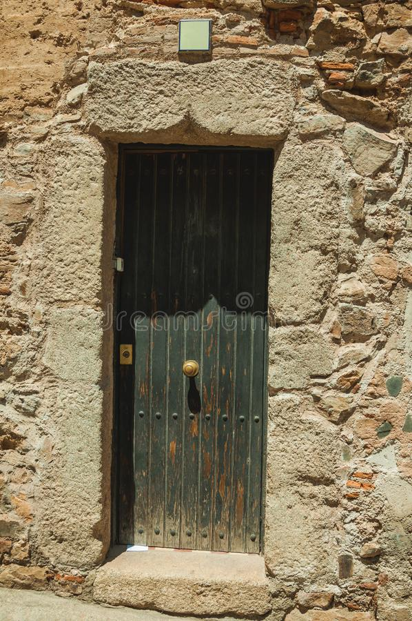 Fachada de construção de pedra velha com a porta de madeira fechado em Caceres foto de stock royalty free