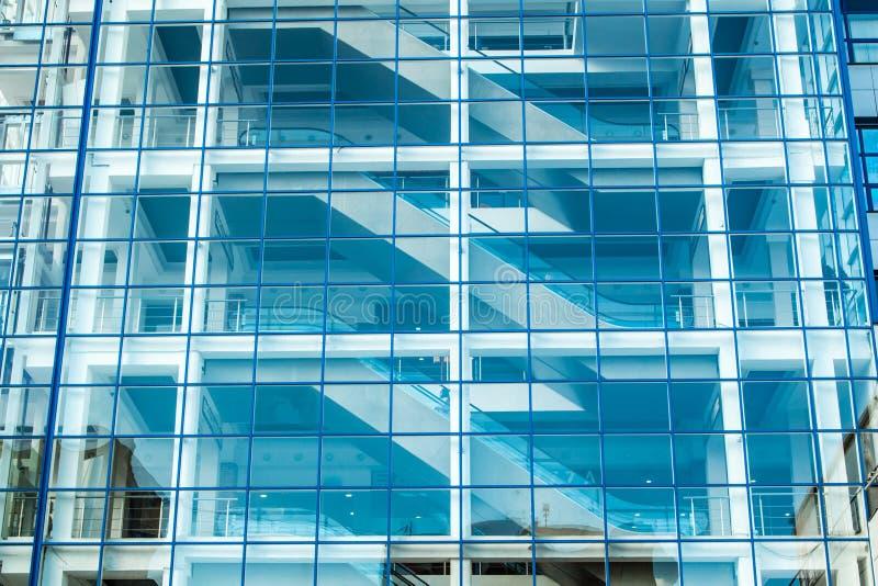 Fachada de cristal del edificio con la escalera móvil fotos de archivo