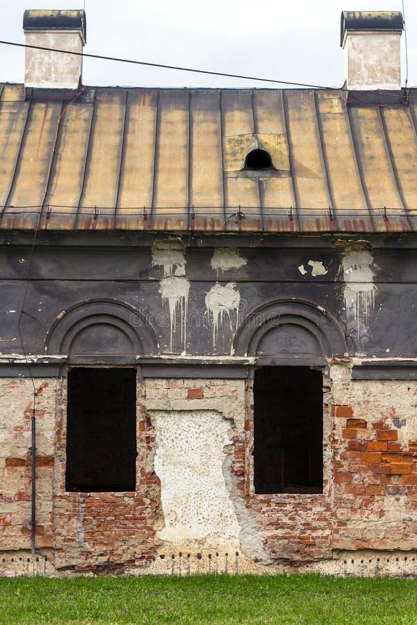 Fachada de la casa abandonada vieja con las ventanas oscuras en Eslovaquia foto de archivo libre de regalías