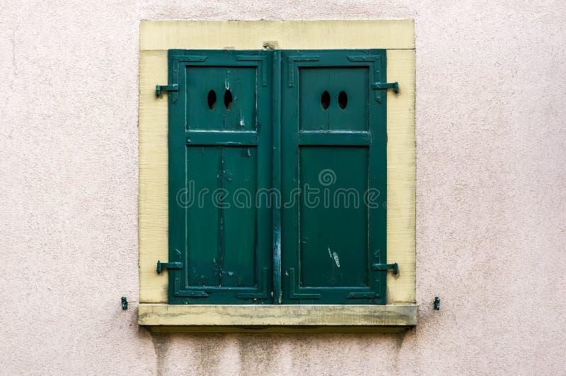 Fachada de la casa con el obturador de madera cerrado verde con 4 aberturas ligeras ovales fotografía de archivo