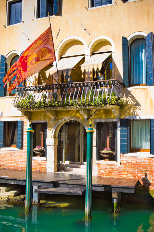 Fachada de la casa medieval típica con la bandera en el canal, Venecia, Italia imagen de archivo