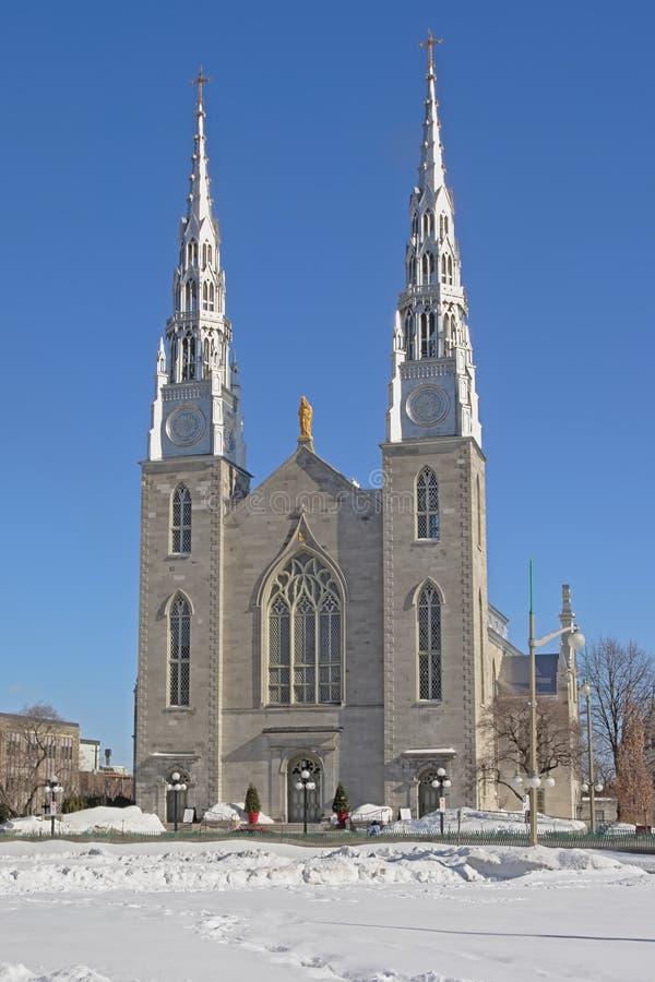 Fachada de la catedral de Notre-Dame en Ottawa en un día de invierno soleado con nieve y el cielo azul claro foto de archivo libre de regalías