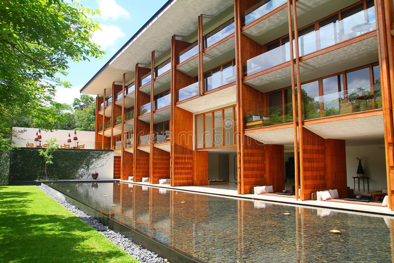 Fachada de madera del edificio de lujo con el jardín y la piscina imagenes de archivo