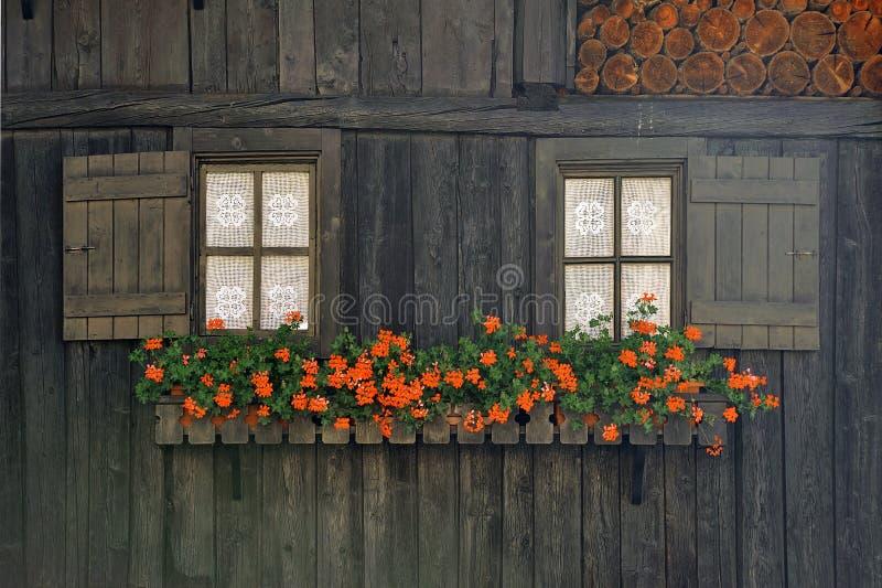 Fachada de madera rural con las ventanas y las flores en la ciudad Rhemes Notre Dame de las montañas imagen de archivo libre de regalías
