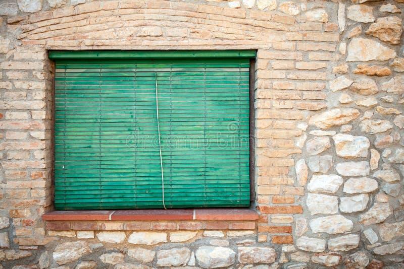 Fachada de pedra velha com os obturadores de madeira verdes na janela fotos de stock